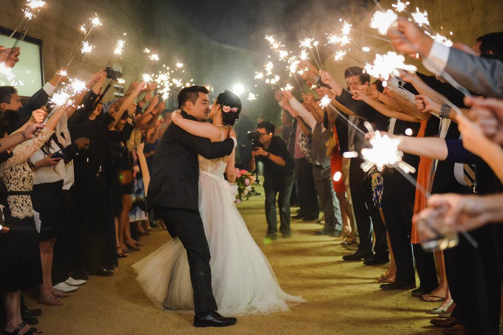 Dreamy pastels dallas texas embrace under guests' sparkler arch