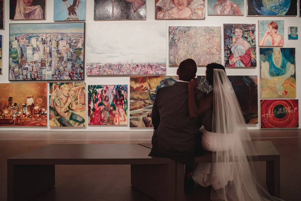 Glam cleveland museum wedding couple sitting on bench looking at paintings