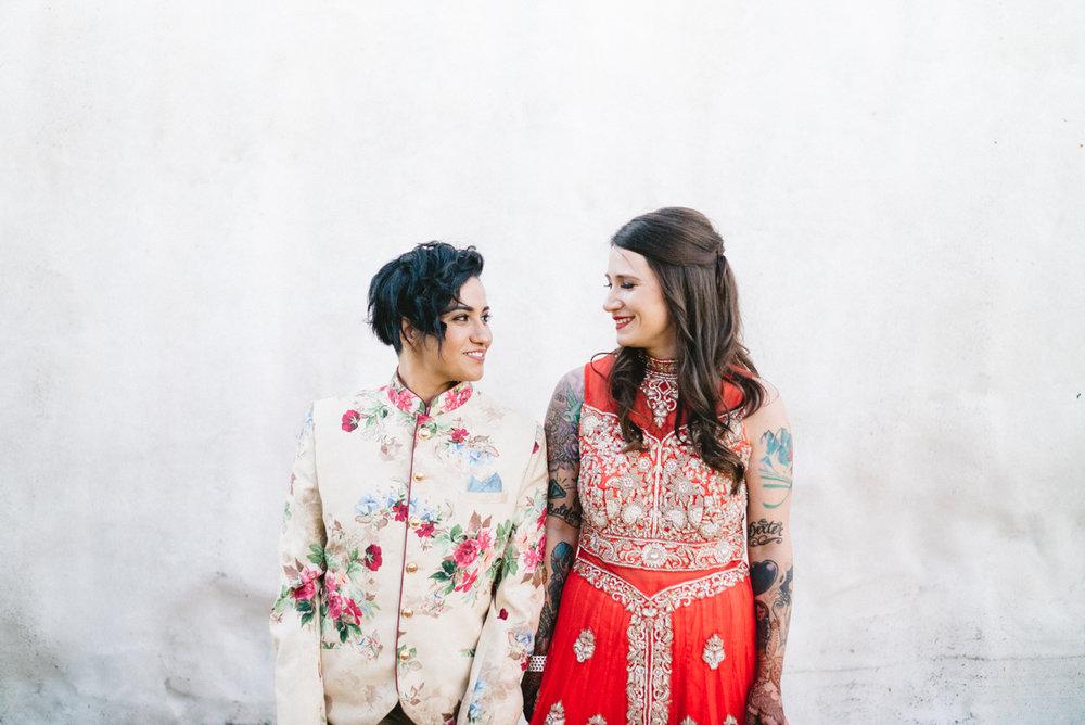 DENVER SAME-SEX INDIAN WEDDING BRIDES SMILING AT EACH OTHER IN FRONT OF LARGE ROCK