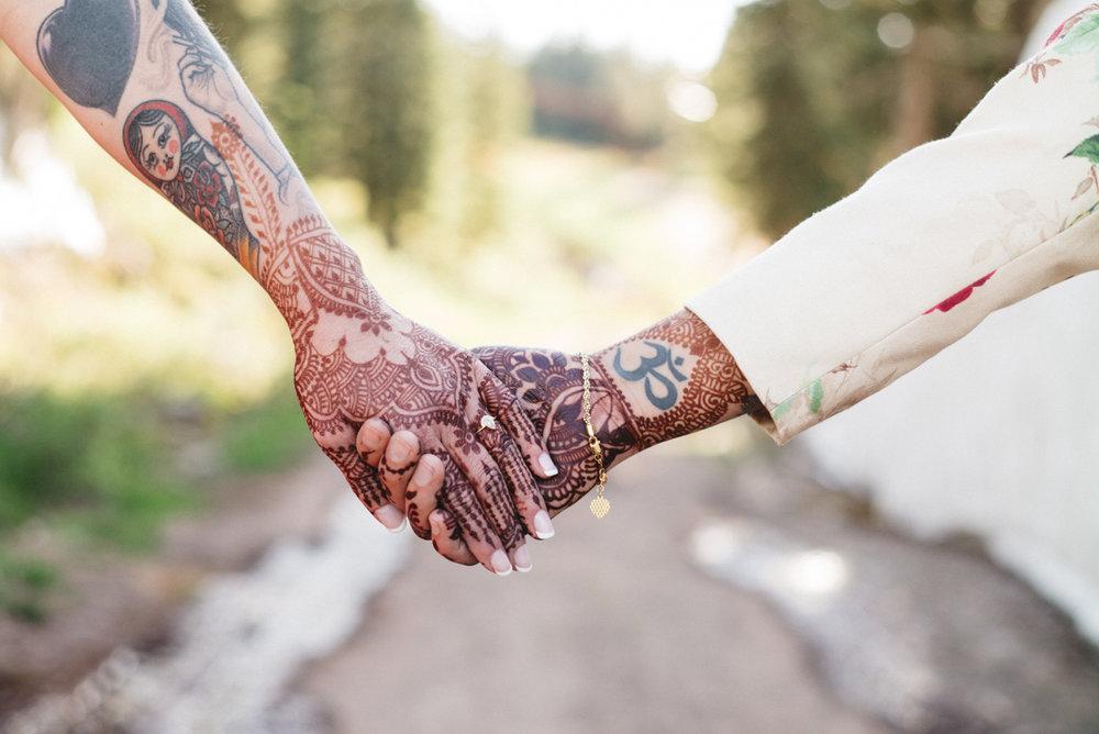 DENVER SAME-SEX INDIAN WEDDING BRIDES HOLDING HENNA-COVERED HANDS