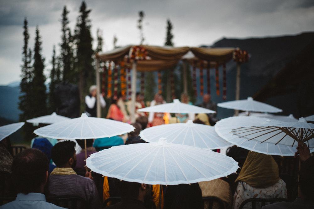 Denver Same-Sex Indian Wedding guests holding paper umbrellas