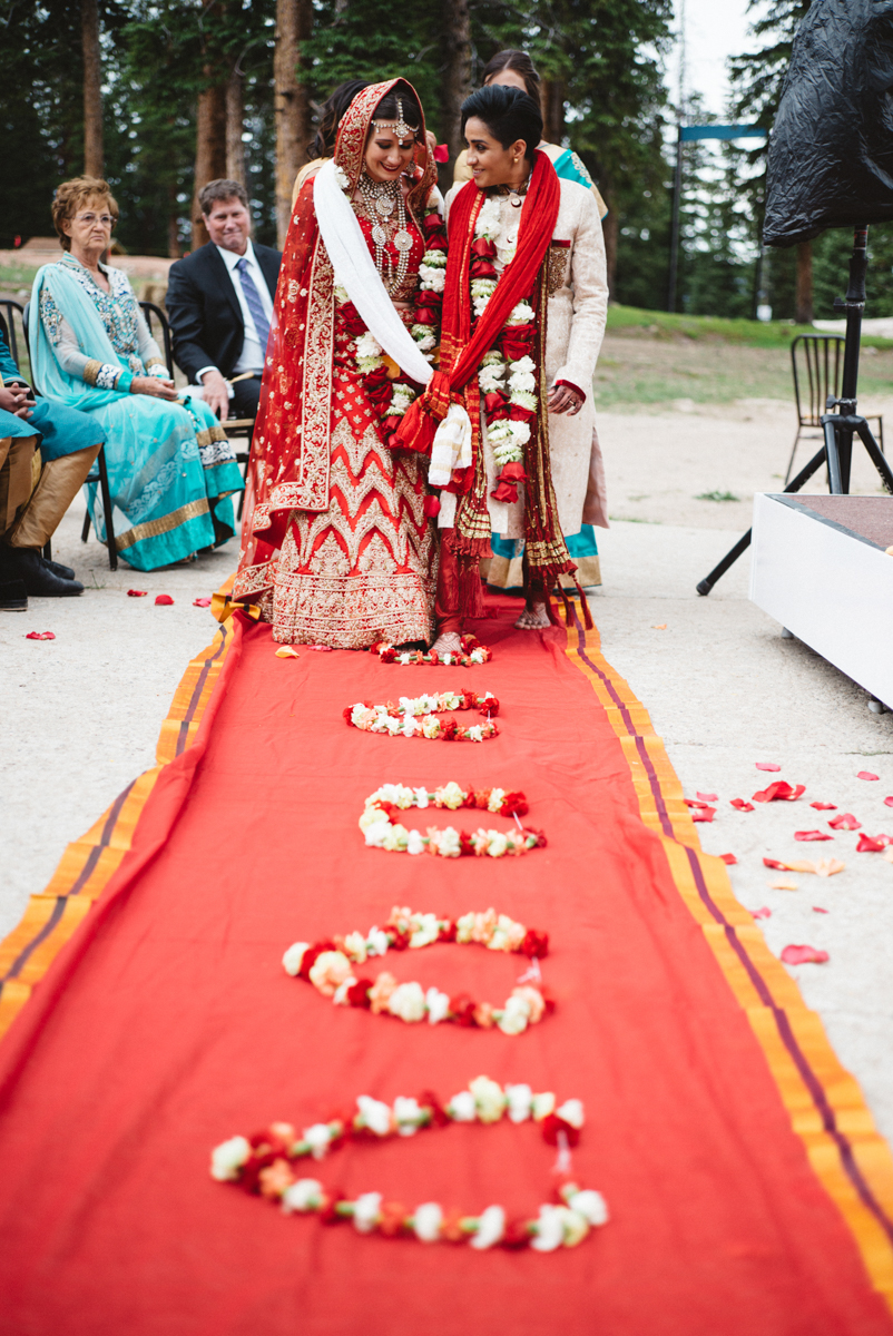 Denver Same-Sex Indian Wedding couple leaving ceremony on carpet strewn with floral garlands