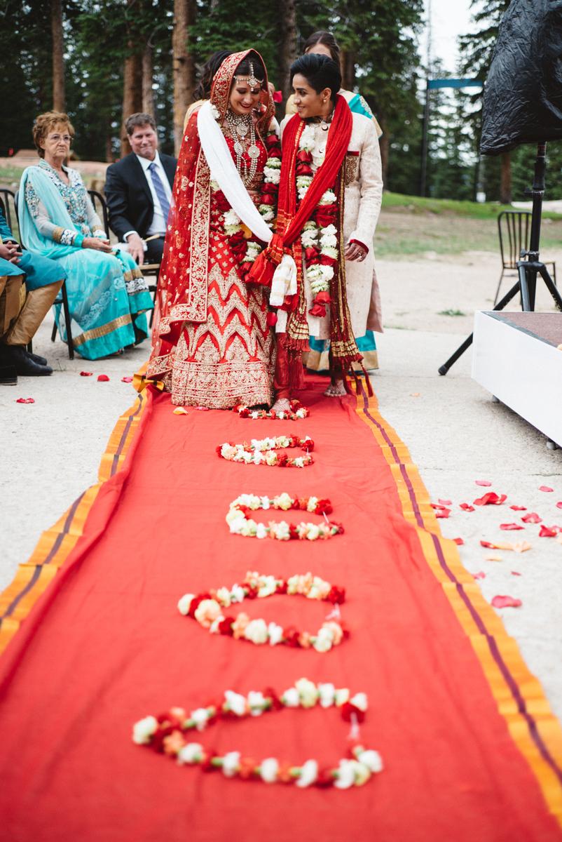 Denver Same-Sex Indian Wedding couple leaving ceremony on carpet strewn with floral garlands