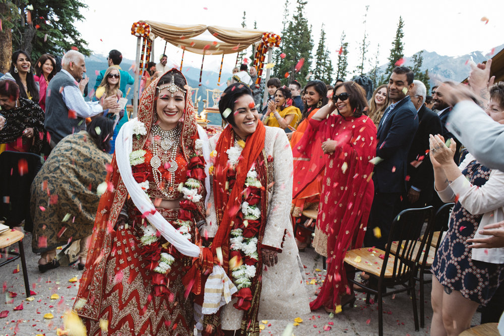 denver same-sex indian wedding couple leaving ceremony being showered in flower petals