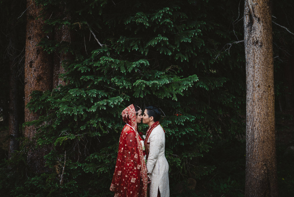 denver same-sex indian wedding kiss by pine trees