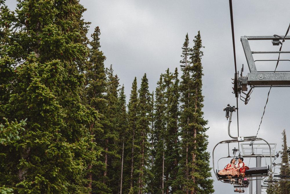 denver same-sex indian wedding couple on ski lift next to pine trees