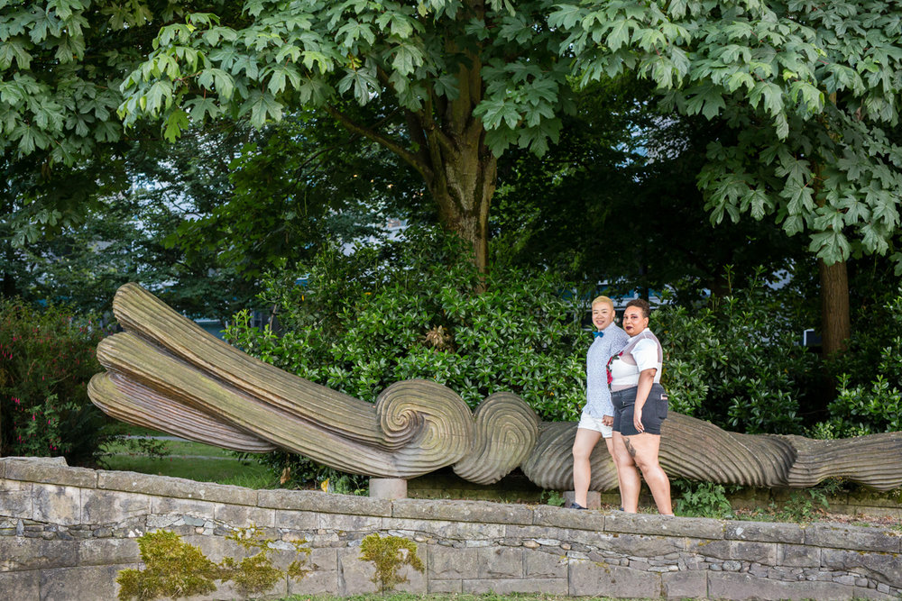 "vancouver ""just because"" photo shoot couple walking in front of park's sculpture"