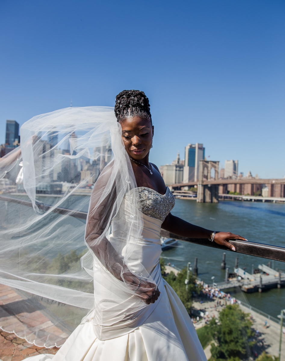 Caribbean NYC wedding sylvia on balcony overlooking river, veil blowing in breeze