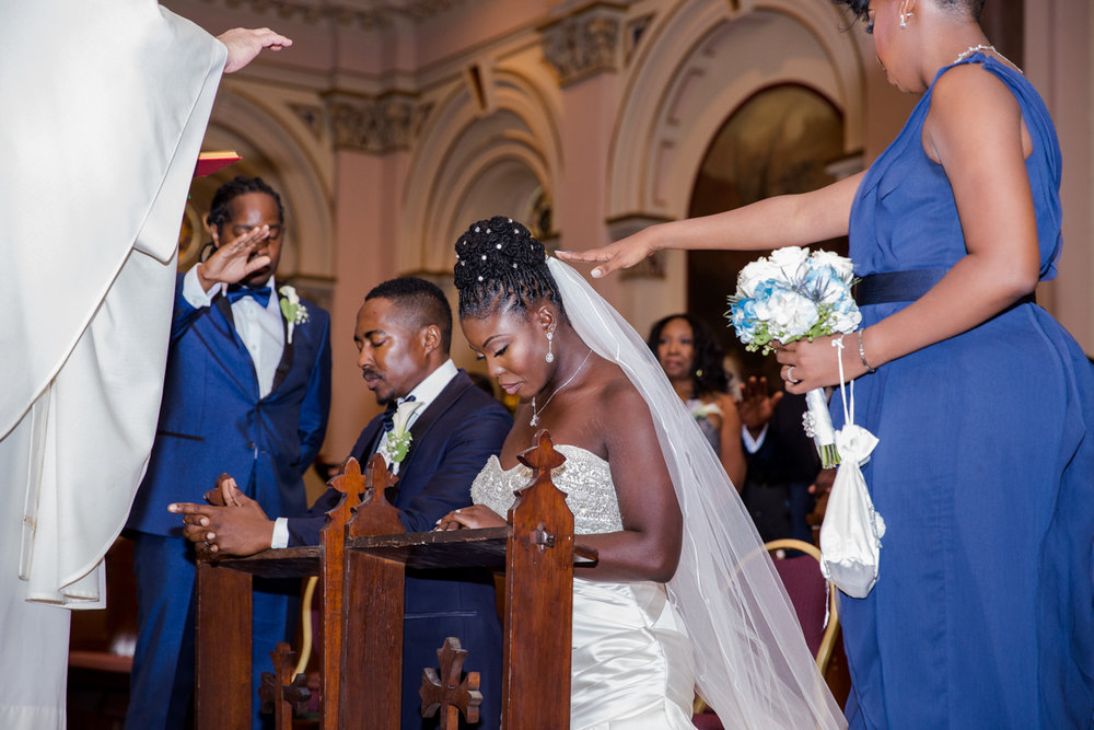 Caribbean NYC wedding couple kneeling to be prayed over