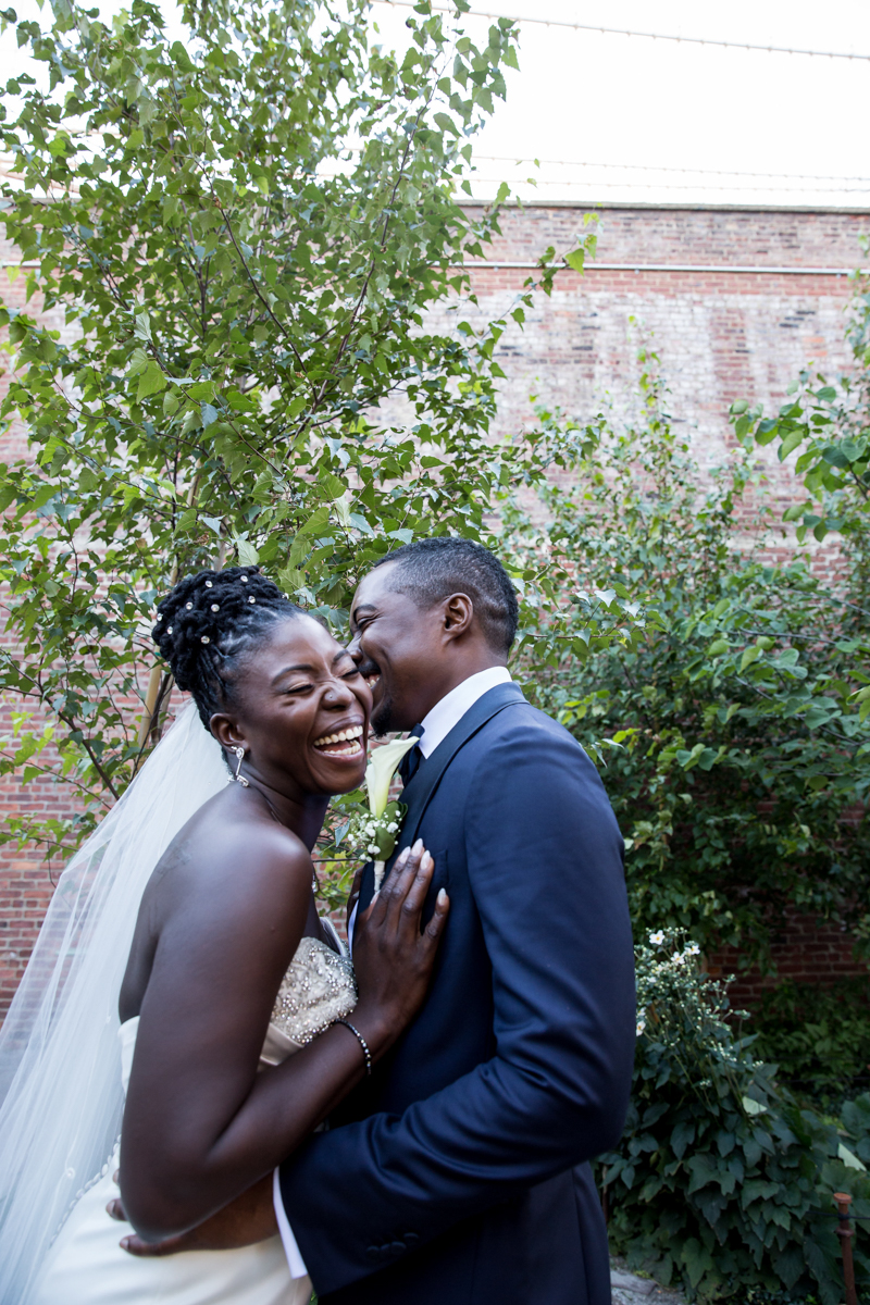 Caribbean NYC wedding embrace in garden while laughing