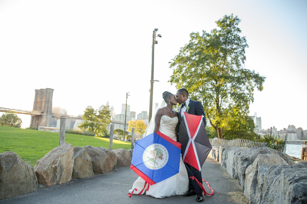 Caribbean NYC wedding kiss in park while holding kites
