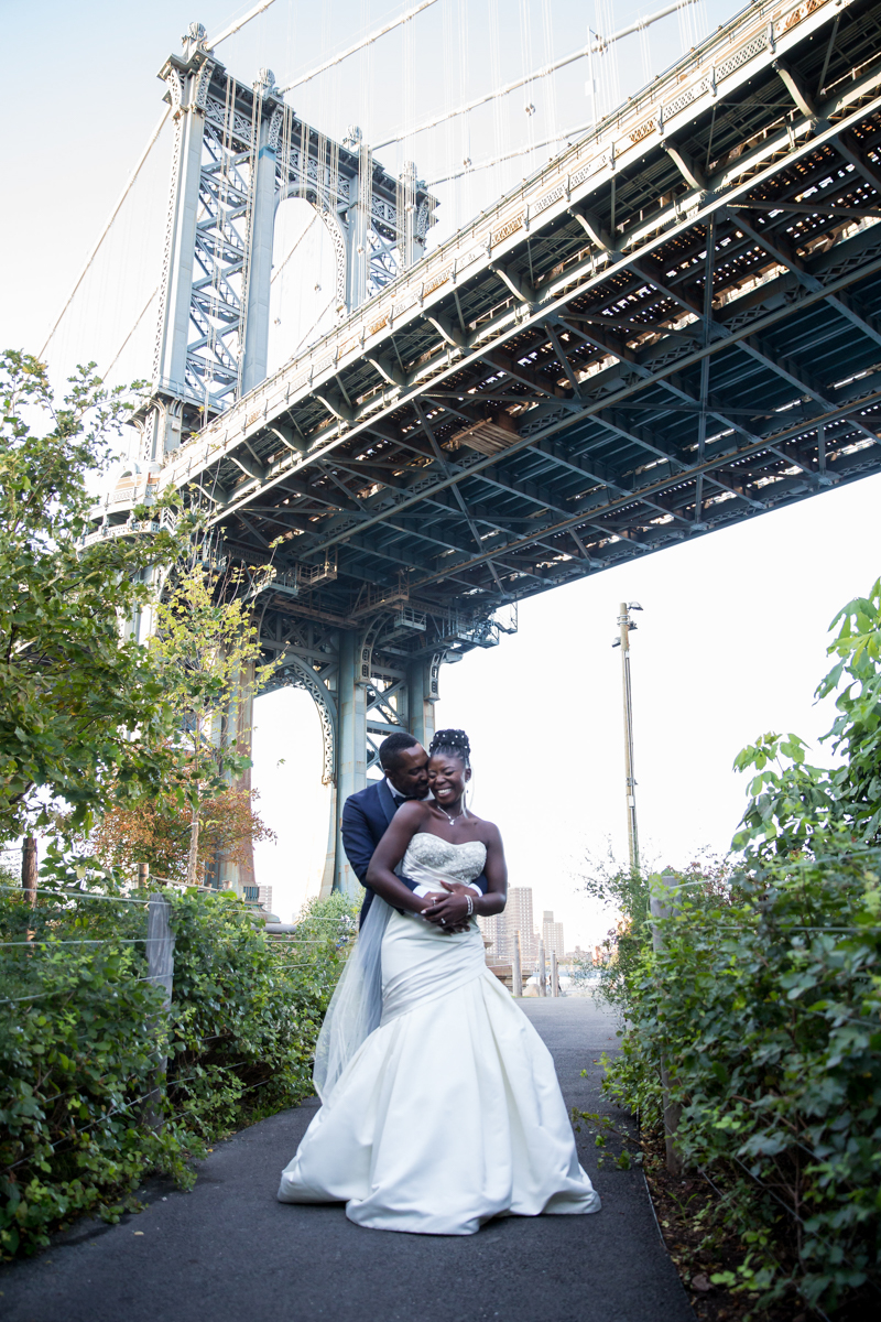 Caribbean NYC wedding embrace on path under bridge