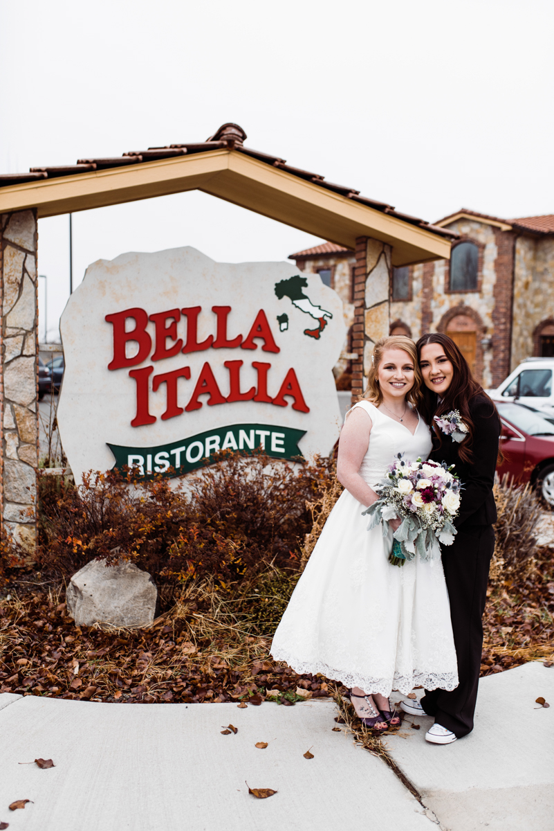 Rustic italian wedding couple in front of sign for bella italia