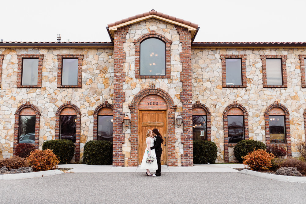 Rustic italian wedding embrace in front of restaurant