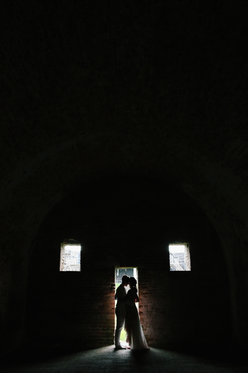 gulf shores destination wedding embrace silhouetted in brick door frame