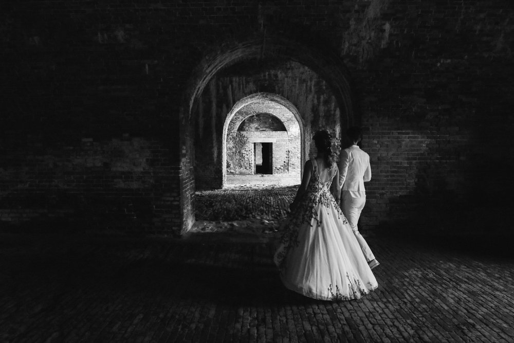 gulf shores destination wedding couple walking through brick arches