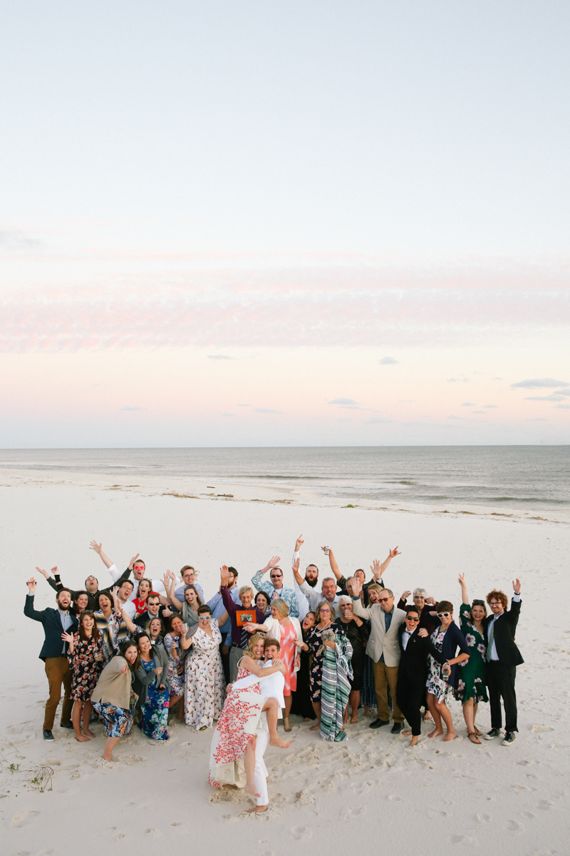 gulf shores destination wedding kate holding ajay in front while guests pose behind them