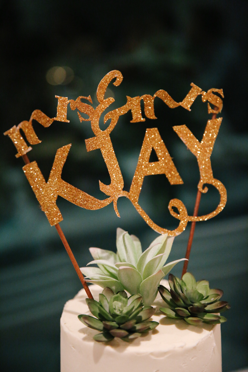 "gulf shores destination wedding cake with glittery cake topper reading ""mrs. and mrs. kjay"""