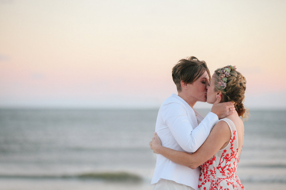 gulf shores destination wedding kiss with ocean waterline in backgrond