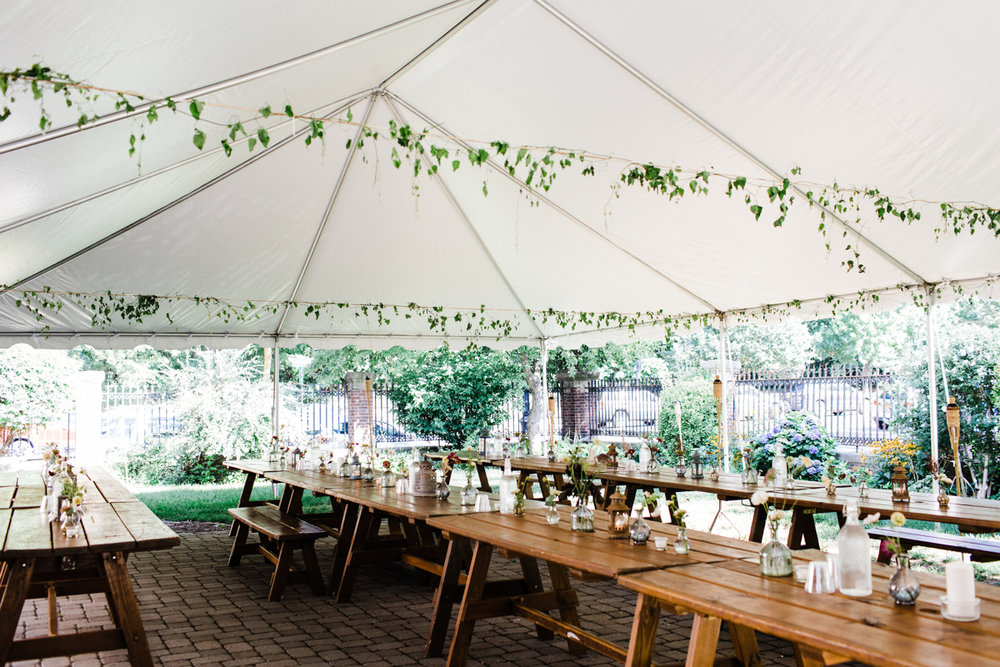 jovial brooklyn ny wedding tent hung with vines over picnic tables