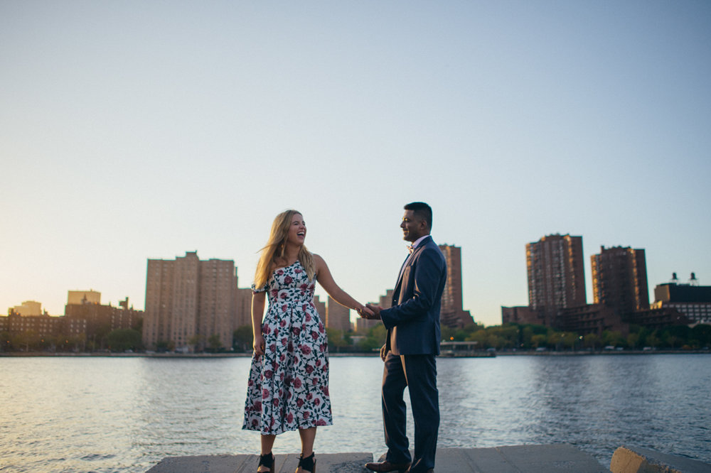 randall's island park engagement jen and hari holding hands and laughing with river and buildings in background