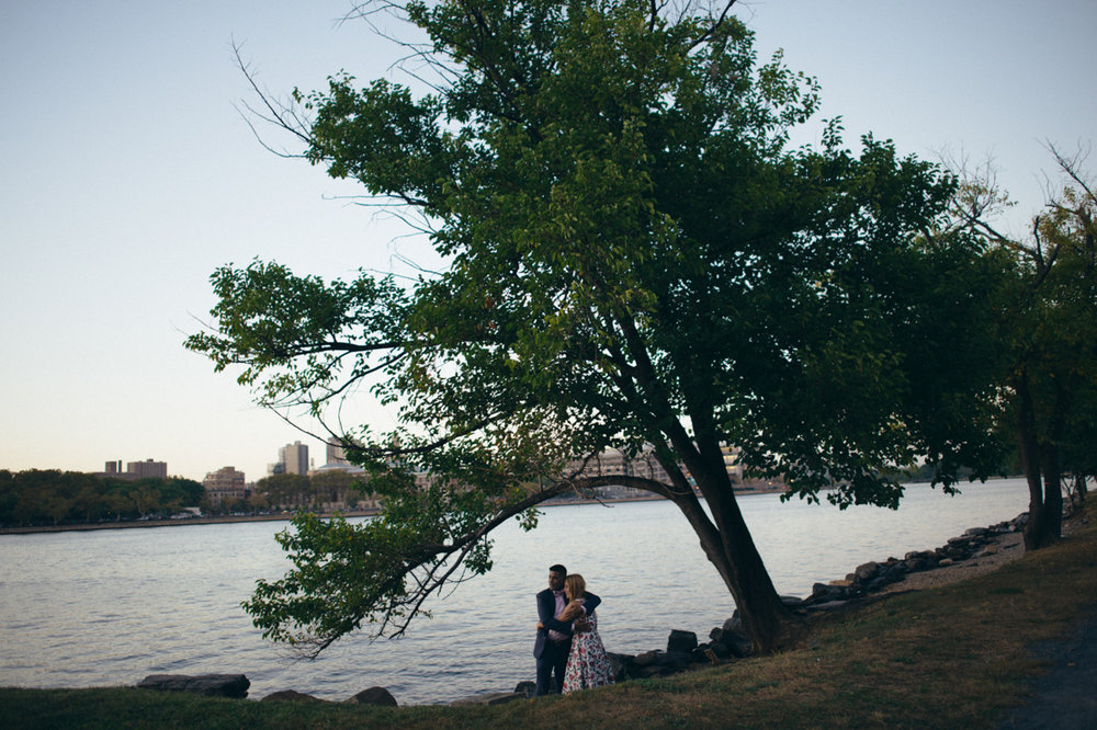 randall's island park engagement wide shot embrace under tree on riverbank