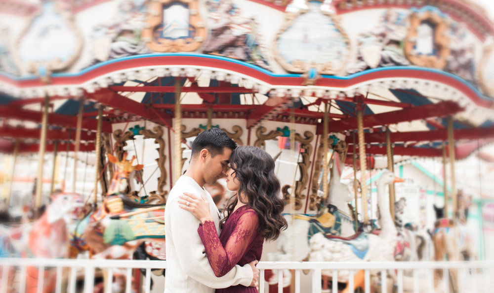 belmont park engagement session san diego embrace in front of merry-go-round