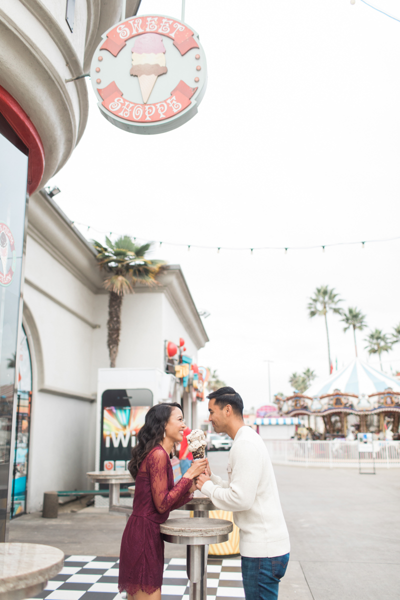 belmont park engagement session san diego couple sharing ice cream cone at outside table of sweets shop