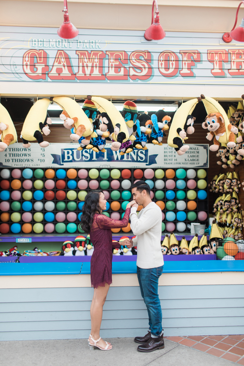 belmont park engagement session san diego jamie kissing angela's hand in front of darts game