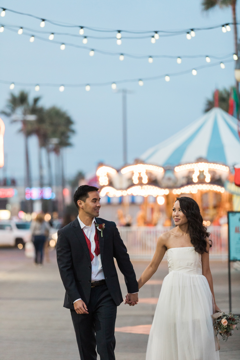 belmont park engagement session san diego couple in wedding clothes at park