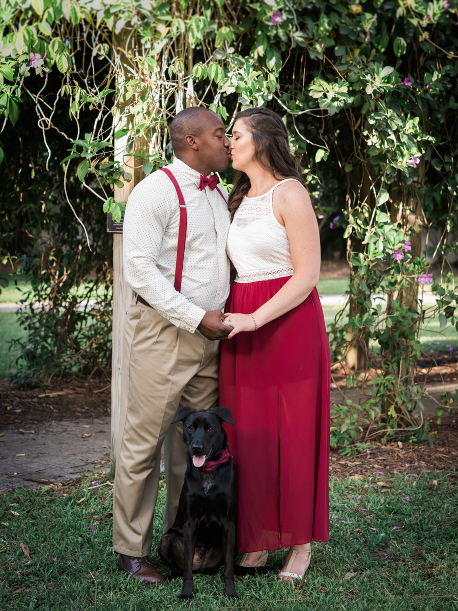 BOCA RATON ENGAGEMENT SESSION KISS UNDER TREES WITH DOG SITTING IN FRONT OF COUPLE