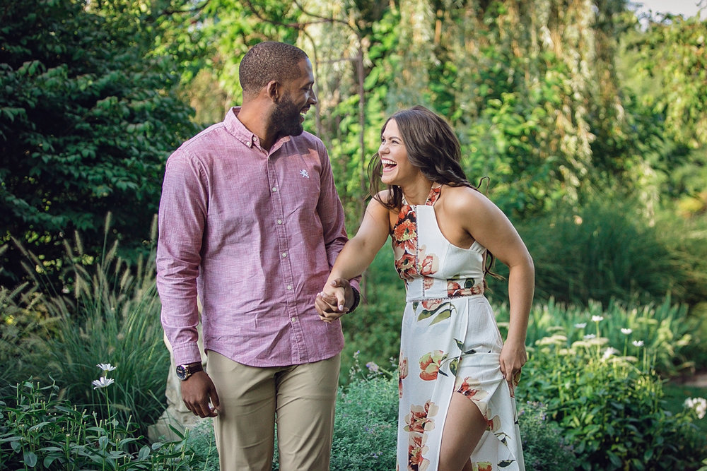 Shelby Township Michigan Garden Engagement laughing candid of genevieve and maurice walking holding hands