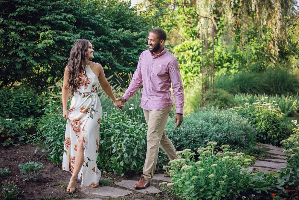 Shelby Township Michigan Garden Engagement couple walking hand in hand down stone path