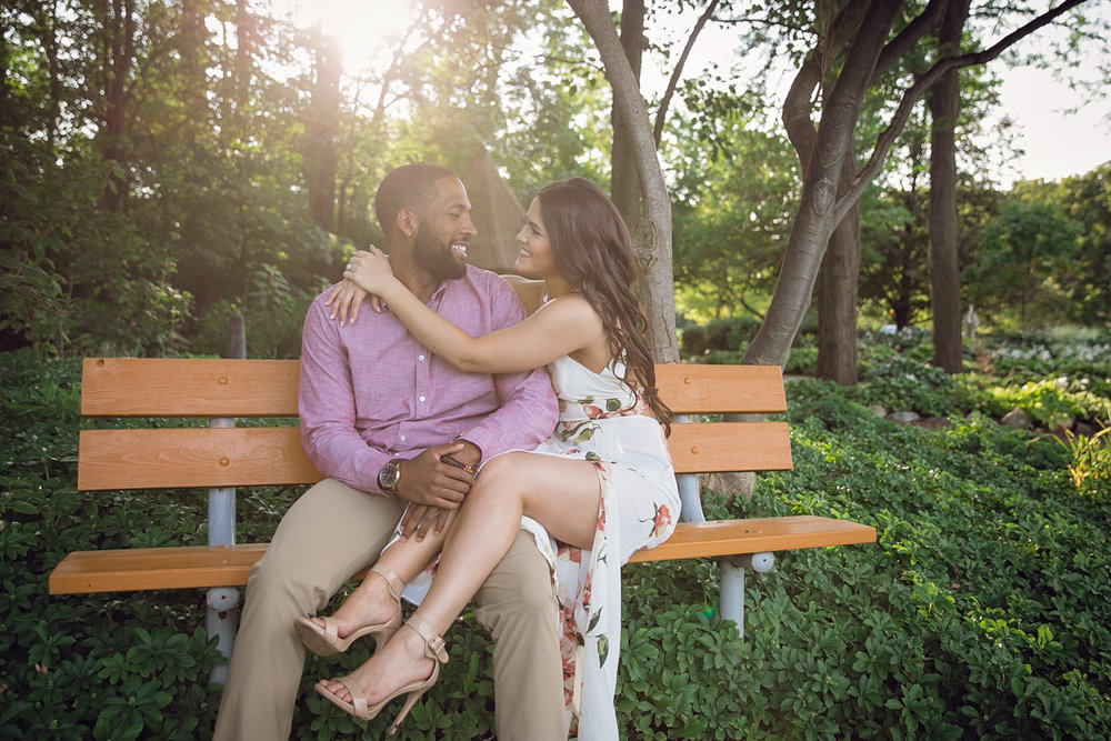 Shelby Township Michigan Garden Engagement couple on bench, genevieve's legs resting over maurice's thigh