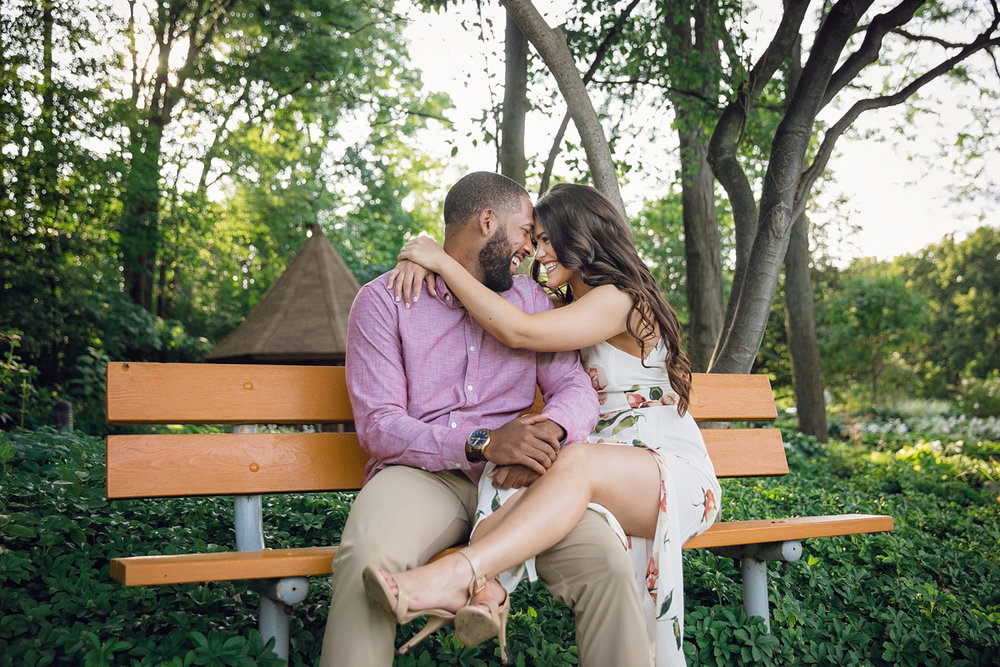 Shelby Township Michigan Garden Engagement embrace on bench, laughing