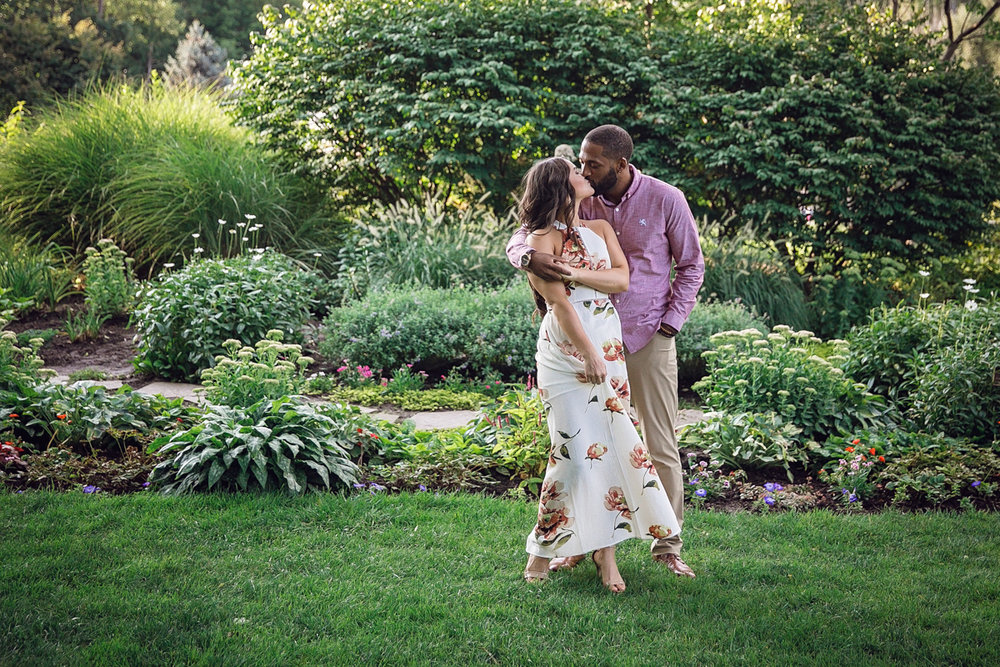Shelby Township Michigan Garden Engagement kiss in grass by garden path