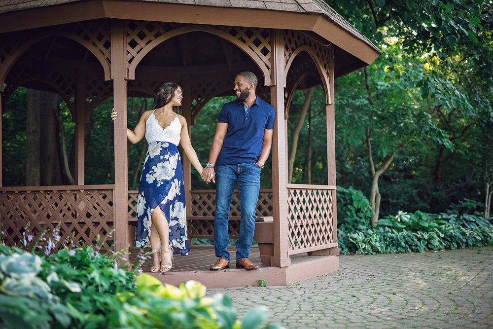 Shelby Township Michigan Garden Engagement couple holding hands and smiling under gazebo