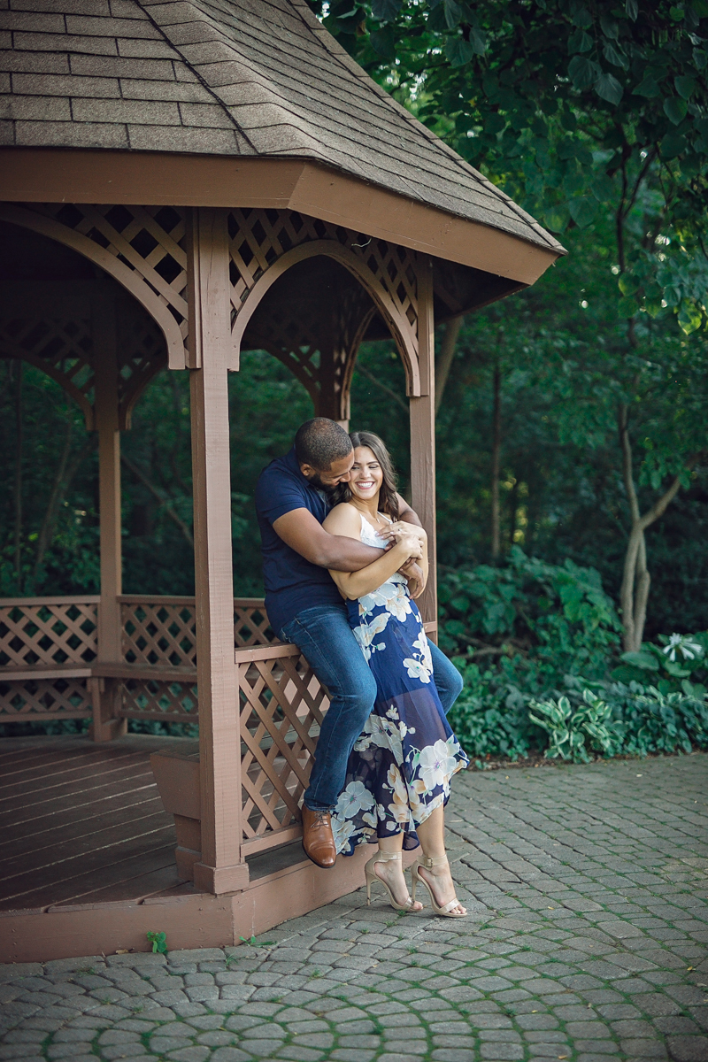 Shelby Township Michigan Garden Engagement embrace smiling, maurice sitting on gazebo ledge and genevieve standing