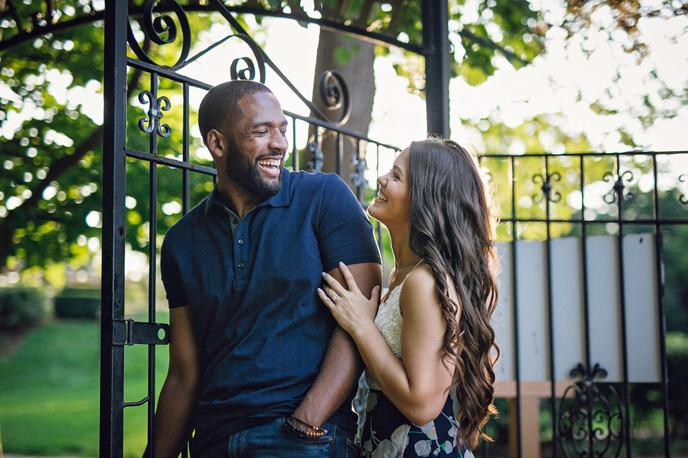 Shelby Township Michigan Garden Engagement laughing in front of iron gate