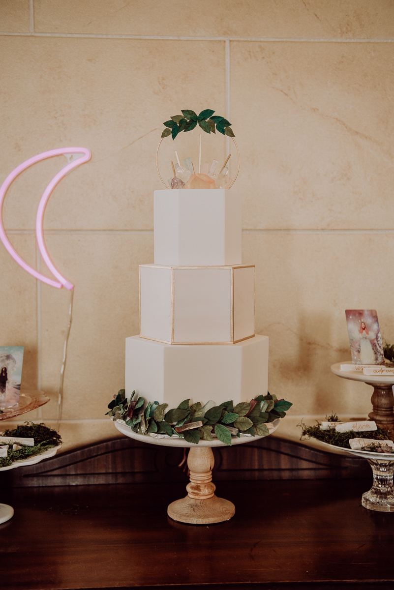 emily bauso styled shoot geometric cake with leaves and crystal cake topper
