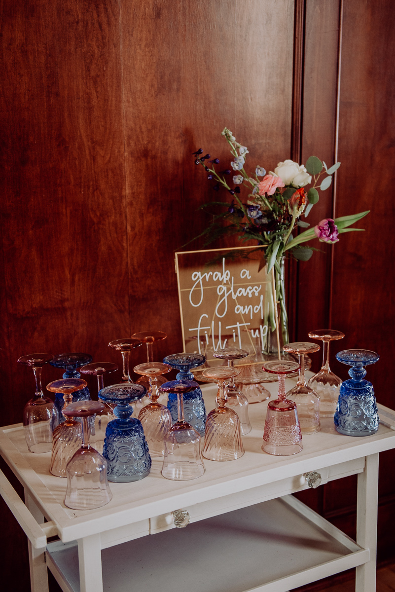 "emily bauso styled shoot table with empty glasses and a sign reading ""grab a glass and fill it up"""