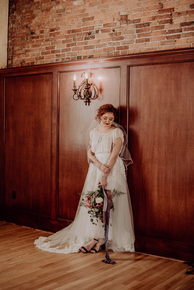 emily bauso styled shoot bride holding bouquet standing under light fixture on wall