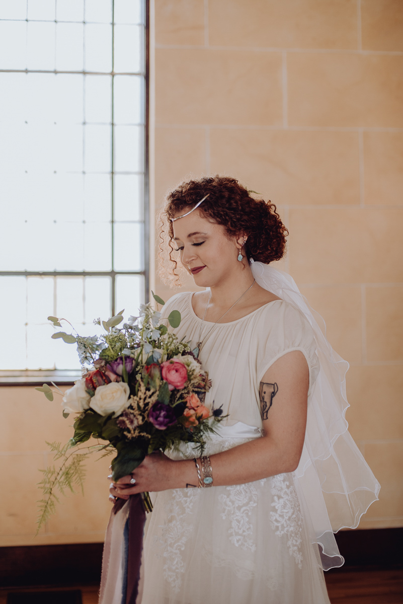 emily bauso styled shoot bride holding bouquet in front of window