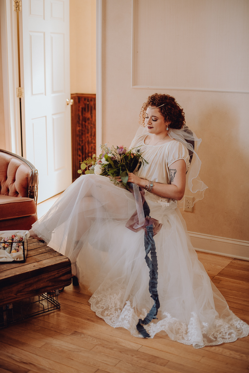emily bauso styled shoot bride in chair holding bouquet