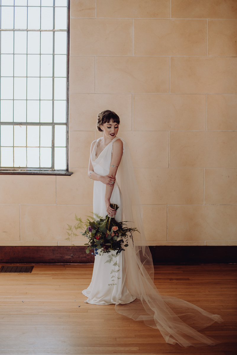 emily bauso styled shoot second bride holding bouquet in front of window