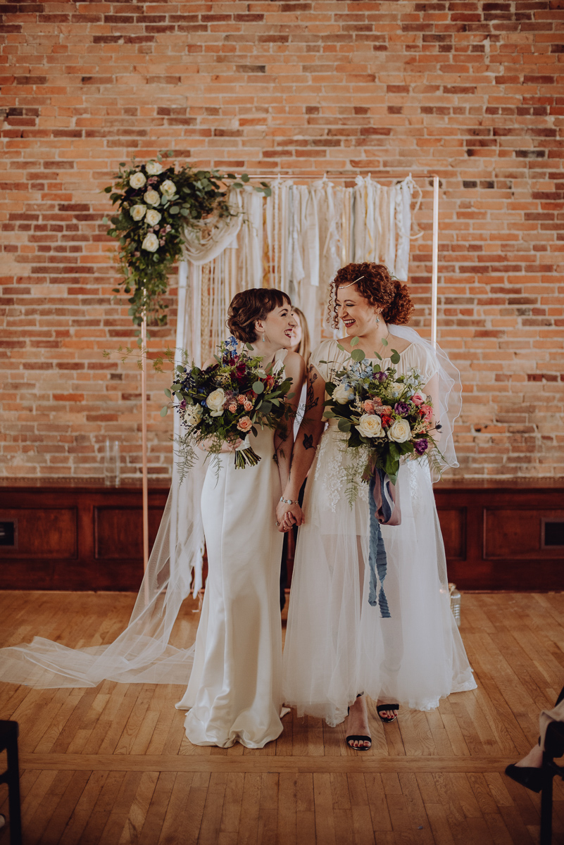 emily bauso styled shoot brides holding hands and smiling at altar