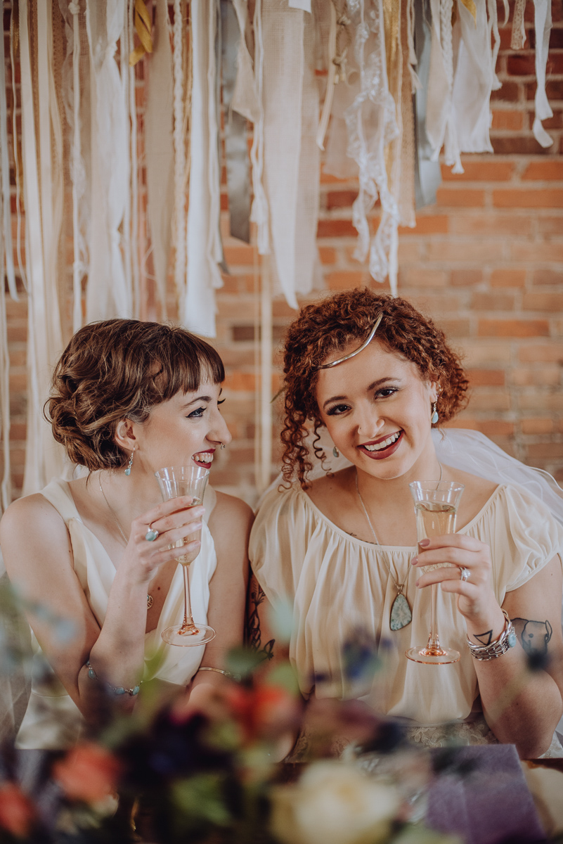 emily bauso styled shoot brides holding champagne head table