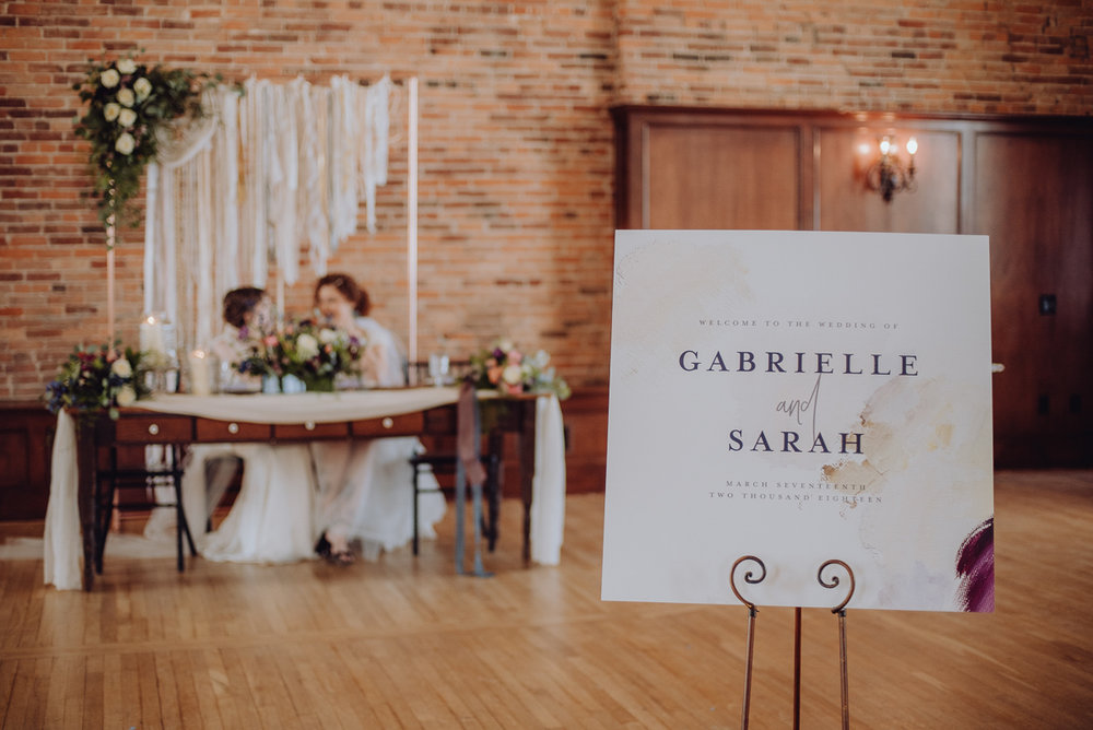 emily bauso styled shoot welcome sign with head table and brides in background