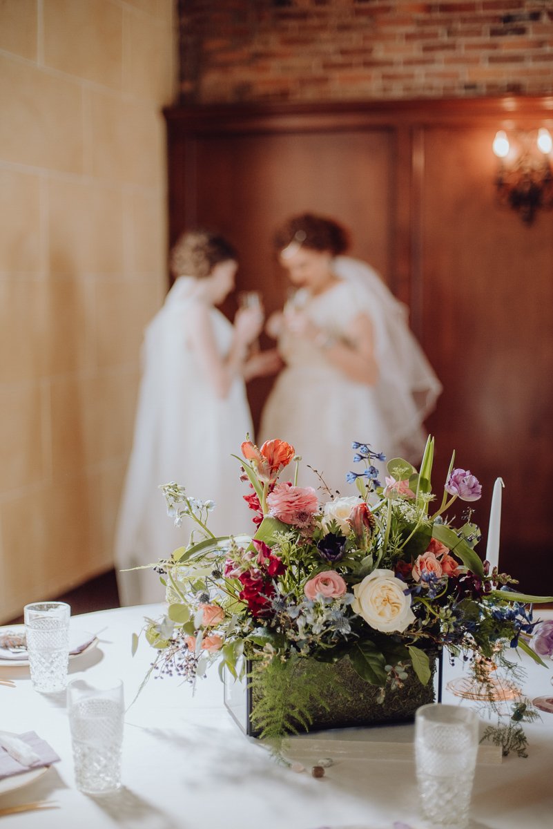 emily bauso styled shoot floral centerpiece with brides standing in background
