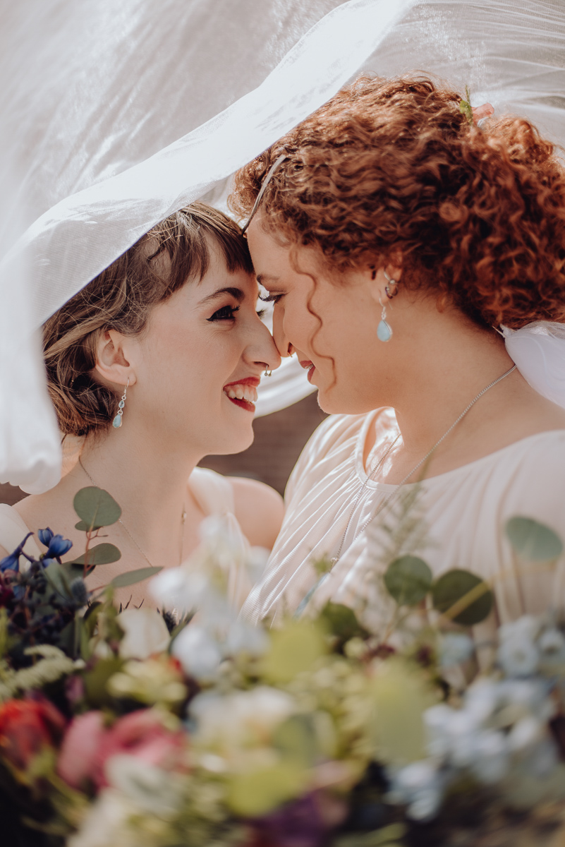 emily bauso styled shoot brides smiling under wedding veil